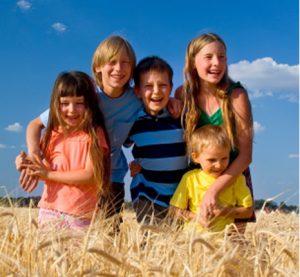 5 kids laughing in a field near Des Moines, Iowa.