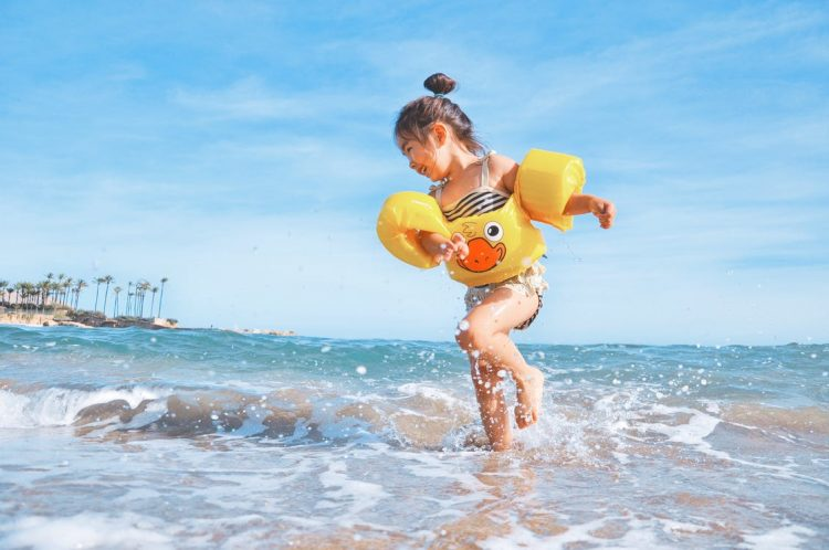 girl splashing at beach wearing floaties