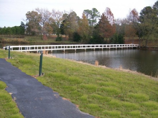 Trinity Pines Bridge that spans the lake - green grass